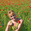 Stock Photo: Portrait of womof average years with red poppy in hand