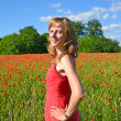 Stock Photo: Portrait of the young woman in a poppy field