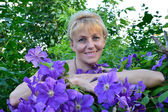 Portrait of the woman of average years among flowers Clematis — Stock Photo