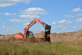 The excavator works at soil relocation — Stock Photo