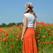 The young woman costs in a poppy field — Stock Photo #32086999