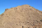 Dump der lehmboden gegen den blauen himmel — Stockfoto