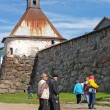 Pilgrims stand near tower of Solovki monastery — Stockfoto #33605877