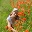 The young woman sits on a grass among red poppies — 图库照片