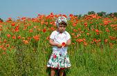 The little girl keeps red poppy in a poppy field — Stockfoto