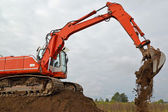 The excavator works at soil movement — Stok fotoğraf