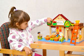 The little girl lefthander plays with Lego — Stock Photo