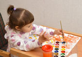 The little girl lefthander draws water color paints — Stock Photo