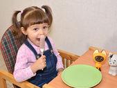 The little girl eats sausage by means of a fork — Stock Photo