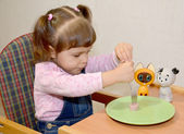 The little girl pins sausage on a fork — Stock Photo
