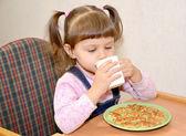 The little girl drinks tea at breakfast — Stock Photo