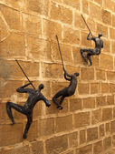 Figures of the people clambering on a wall. Yaffo, Israel — Stock Photo