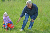 The grandfather rolls the granddaughter on the toy car (focus on — Stock Photo