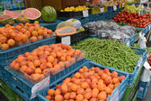 Fruit and vegetables lie in boxes on a market counter — Stock Photo