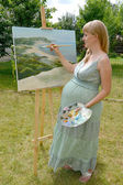 The young pregnant female artist draws a picture oil paints in t — Stock Photo