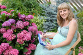 The young pregnant female artist draws water color paints a blos — Stock Photo