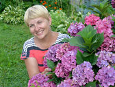 The happy woman of average years near a blossoming hydrangea in  — Stock Photo