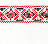 Red ornament stitched on linen background — Stock Photo