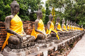 Stone Buddha statue in row — Stock Photo