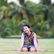 Asian woman sit and smile in park — Stock Photo