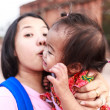 Asian woman kissing her daughter — Stock Photo #26143317