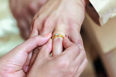 Bride wearing ring on groom's finger — Stock Photo