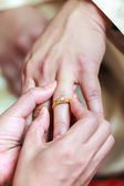 Bride wearing ring on groom's finger — Foto Stock