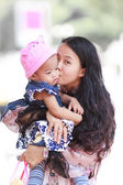 Asian woman holding and kissing baby — Stock Photo