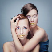 Portrait of two girls with golden lips — Stock Photo