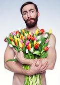 Portrait of sad man with flowers. — Stock Photo
