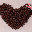 Dark roasted coffee beans  in the shape of a heart with a red bo — Zdjęcie stockowe