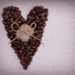 Dark roasted coffee beans  in the shape of a heart with  bow on - Stock Photo
