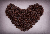 Dark roasted coffee beans in the shape of a heart — Stock Photo