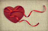 A red wooden heart with a ribon bow on vintage fabric backgroun — Stock Photo