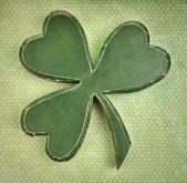 Green wooden shamrock on vintage polka dot texture — Stock Photo
