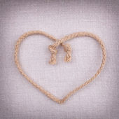 A love heart made of string on fabric vintage background — Stock Photo