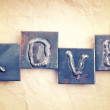 The word LOVE made from metal letters on an old vintage paper — Stock Photo