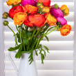 Flowers in a vase with sun light coming out of window blinds — Photo