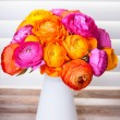 Flowers in a vase on wooden table with sun light coming out of w — Stock Photo