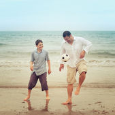 Father and son having fun on the beach with a ball — Stock Photo