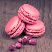 Macaroons with dry roses on retro vintage wooden background — Photo