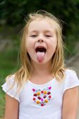 Cute girl with put out tongue — Stock Photo