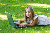 Cute girl with laptop on green grass — Stock Photo