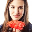 Teenage girl holding flower close to face — Stock Photo