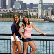 Two sisters interacting with city behind — Stock Photo