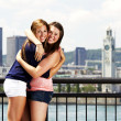 Royalty-Free Stock Photo: Two sisters interacting with city behind