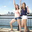 Two girls posing on city scape - Stok fotoraf