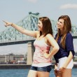 Two sisters interacting with bridge behind — Stock Photo
