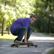 Young teenager rolling around on his longboard — Stockfoto