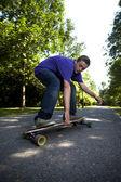 Jovem adolescente rolando seu longboard — Fotografia Stock